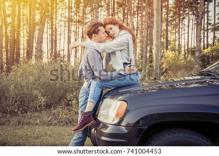 Travel. Couple hugging and kissing on the car's bonnet