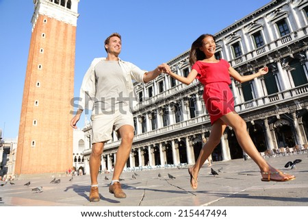 Travel couple in love having playful fun in Venice holding hands running laughing in Venice, Italy on Piazza, San Marco. Happy young couple on travel vacation on St Mark's Square. Happy woman and man. - stock photo