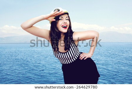 Travel, cruise, tourism and people concept - pretty smiling sailor woman saluting against the sea - stock photo