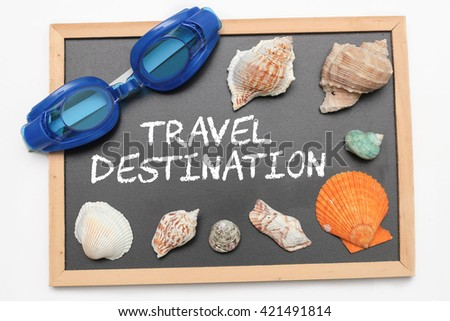 Travel Destination text on chalk board with swimming goggle and shell - vacation and business concept - stock photo