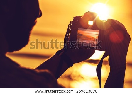 Travel Digital Photography Concept Photo with Men Playing His Professional Digital SLR Camera During Sunset. - stock photo
