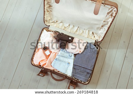 Travel: female brown suitcase with clothes for travel - stock photo