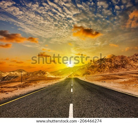 Travel forward concept background - road in Himalayas with mountains and dramatic clouds on sunset. Ladakh, Jammu and Kashmir, India