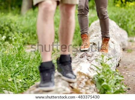 travel, hiking, backpacking, tourism and people concept - close up of couple legs walking along fallen tree trunk outdoors
