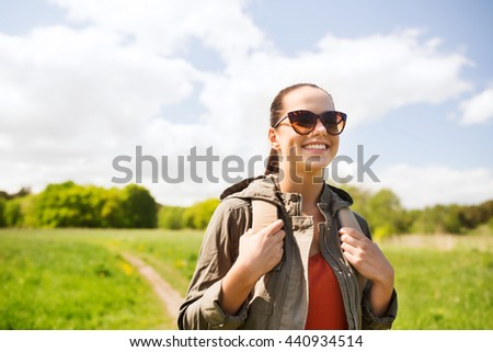 travel, hiking, backpacking, tourism and people concept - happy young woman in sunglasses with backpack walking along country road outdoors - stock photo