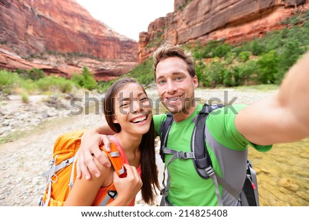 Travel hiking selfie self-portrait photo by happy couple on hike. Active lifestyle with hikers friends or lovers smiling at camera in Zion National Park, Utah, USA. Young Asian woman and Caucasian man - stock photo
