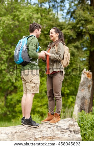 travel, hiking, tourism, love and people concept - happy couple with backpacks holding hands outdoors