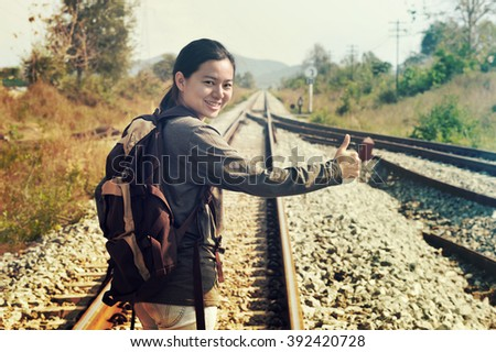 Travel hitchhiker woman backpacking hitchhiking thumbing happy walking on rail side during holiday travel - stock photo