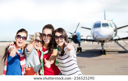 travel, holidays, vacation, happy people concept - smiling teenage girls or young women showing thumbs up at airport - stock photo