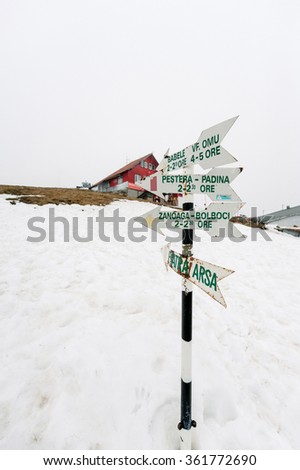 Travel in Romania - wooden signpost in snow above Romanian ski resort village with directions and time to Varful Omu, Babele, Pestera Padina, Zanoaga Bolboci, Piatra Arsa