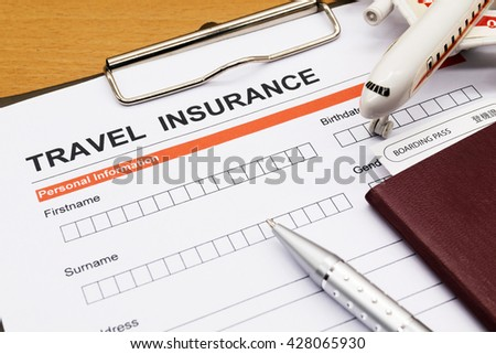 Travel insurance application form with plane model and pen and passport