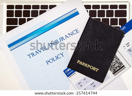 Travel insurance policy booklet with a boarding pass and a passport  - stock photo