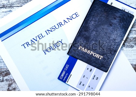 Travel insurance policy booklet with a boarding pass and a passport