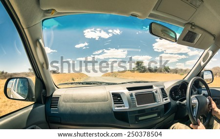 Travel journey from a car cockpit - Concept of adventure trip on the road to namibian exclusive destinations - Fisheye view on desert freeway in Namibia - Soft focus on landscape and clouds - stock photo