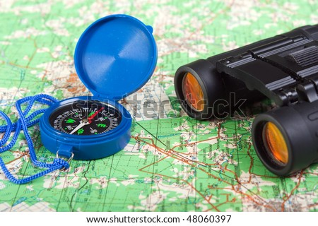 Travel north map direction compass and binoculars - stock photo