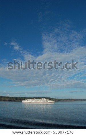 Travel on Lake Ladoga. Clear day. The calm expanse of water. Cruise ship on the sea and the sky. White ship in the distance.