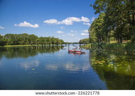 Travel on the lakes on the red kayak - stock photo