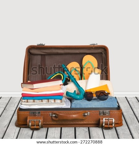 Travel. Packed vintage suitcase full of vacation items - stock photo