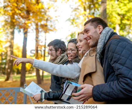 travel, people, tourism, gesture and friendship concept - group of smiling friends with map standing on bridge and pointing finger in city park - stock photo