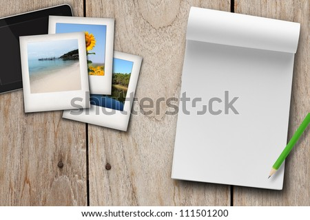 travel plan blank book with photo and tablet on wood table.