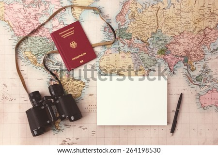 Travel planning - map with passport, notepad, pen and binoculars - stock photo