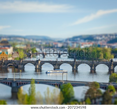 Travel Prague concept background - elevated view of bridges over Vltava river from Letna Park with tilt shift toy effect shallow depth of field. Prague, Czech Republic - stock photo