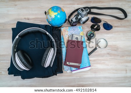 Travel preparation : compass, money, passport, road map ,sunglasses,magnifying glass ,camera ,cloth on wooden table