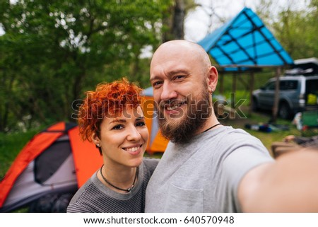 Travel selfie photo by smiling happy couple near camping tent. Hiking self-portrait man and woman outdoors. Active lifestyle friends or lovers in national park. Travelers family enjoy nature holidays.