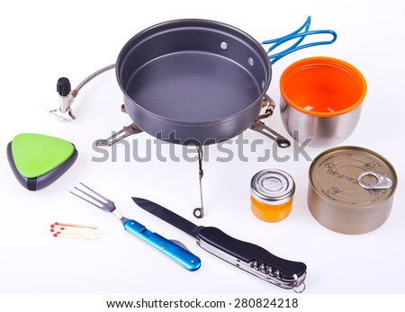 Travel set for eating. Tourist's dish kit. Various professional tools and items for outdoors cooking on white background, partly isolated with shadows - stock photo