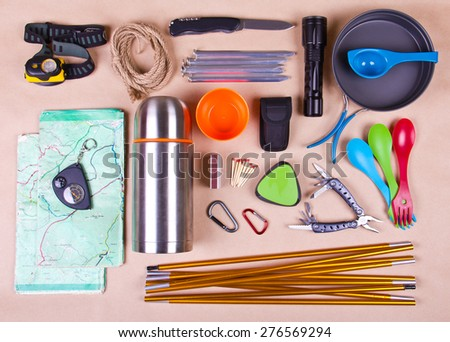 Travel set. Tourist outfit for camping or hiking. Various professional tools and items for outdoors pastime on beige background. - stock photo