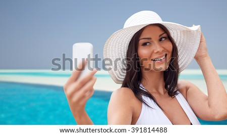 travel, summer, technology and people concept - sexy young woman taking selfie with smartphone over beach and swimming pool background - stock photo