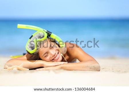 Travel summer vacation beach woman with snorkel. Smiling beautiful young woman relaxing lying on white beach sand in the summer sun with a blue ocean. Photo from Hapuna beach, Big Island, Hawaii, USA. - stock photo