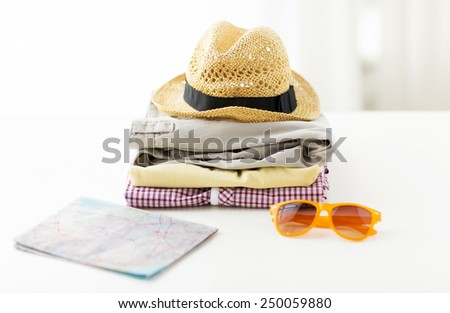 travel, summer vacation, tourism and objects concept - close up of folded clothes and touristic map on table at home - stock photo