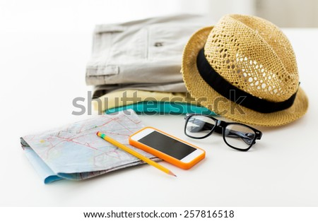 travel, summer vacation, tourism and objects concept - close up of folded clothes, smartphone and touristic map on table at home - stock photo