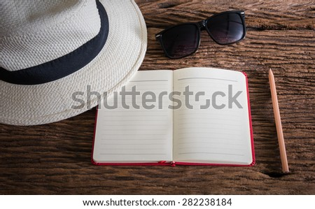 travel, summer vacation, tourism and objects concept. close up of hat, notebook, pencil and sunglasses on wooden table. Photo retro style - stock photo