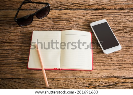 travel, summer vacation, tourism and objects concept. close up of notebook, pencil, smartphone and sunglasses on wooden table. Photo retro style - stock photo