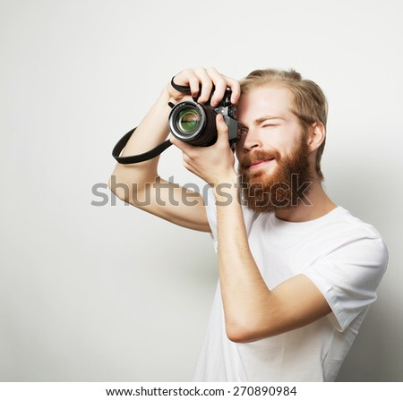 Travel, technology and life style concept: young bearded  photographer taking pictures with digital camera. - stock photo