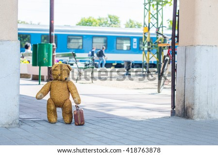 Travel teddy bear on a train station with little luggage