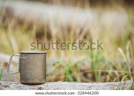 Travel titanium cup on wood on forest background. Lunch during the journey to the wild. Camping lifestyle. - stock photo