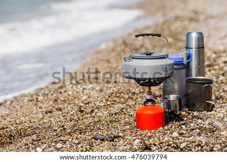 Travel, tourism and camping equipment. Picnic rest, cooking on the nature. Gas stove, kettle with tea or coffee, cup and thermos.