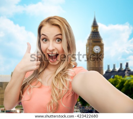 travel, tourism, emotions, expressions and people concept - happy smiling young woman taking selfie and showing thumbs up over big ben london and city background - stock photo