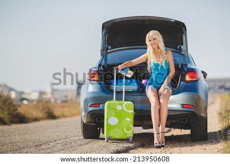Travel, tourism - Girl ready for the travel for summer vacation. Young female sitting in the trunk of a car with suitcases, showing thumb up sign, ready to leave for vacations - stock photo