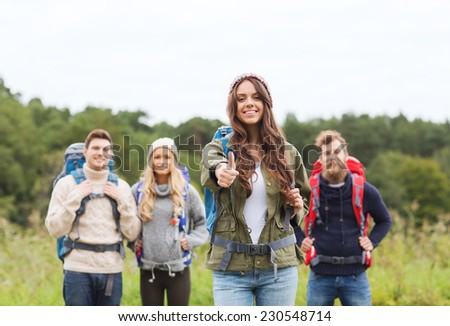 travel, tourism, hike, gesture and people concept - group of smiling friends with backpacks standing and showing thumbs up outdoors - stock photo