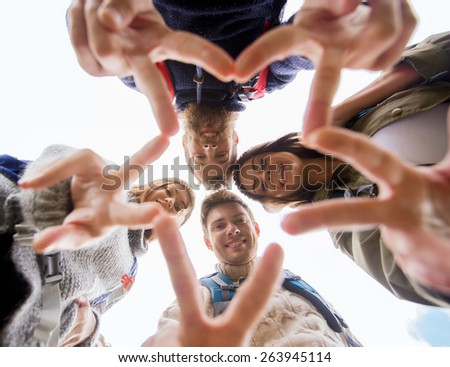 travel, tourism, hike, gesture and people concept - group of smiling friends with backpacks standing in circle and showing victory sign outdoors - stock photo