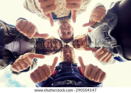 travel, tourism, hike, gesture and people concept - group of smiling friends with backpacks standing in circle and showing thumbs up outdoors