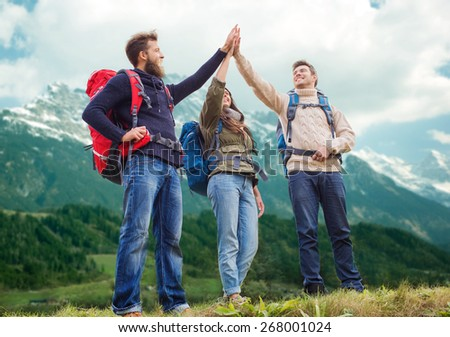travel, tourism, hike, gesture and people concept - group of smiling friends with backpacks making high five over alpine mountains background - stock photo