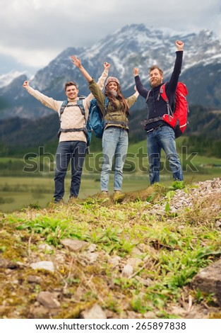 travel, tourism, hike, gesture and people concept - group of smiling friends with backpacks raising hands over mountains background - stock photo