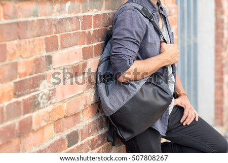 travel, tourism, lifestyle and people concept - close up of man with backpack standing at city street wall