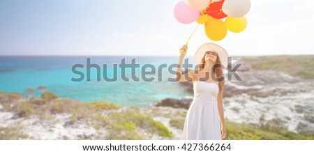 travel, tourism, summer, holidays and people concept - smiling young woman wearing sunglasses with balloons over exotic tropical beach and sea background - stock photo