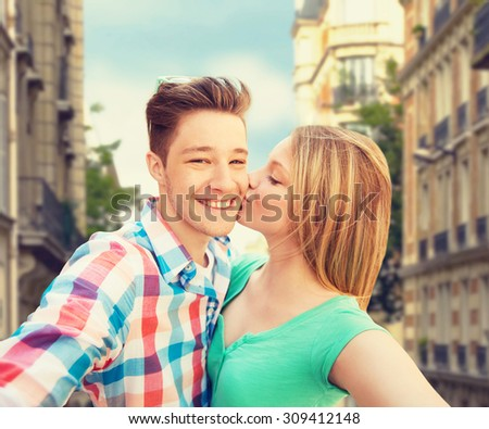 travel, tourism, summer vacation, technology and love concept - happy couple taking selfie with smartphone or camera and kissing over city street background - stock photo